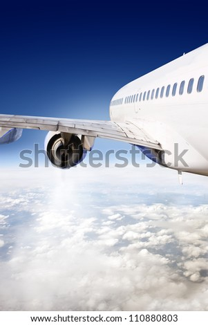 Commercial airliner in flight, seen from the rear wing of the aircraft - stock photo