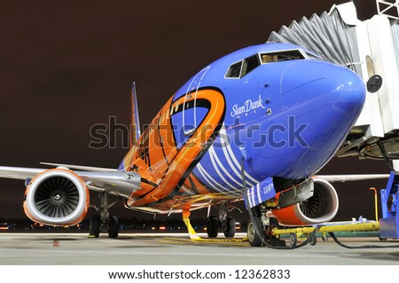 Commercial airplane at the airport at night - stock photo