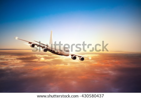 Commercial airplane flying above clouds in dramatic sunset light - stock photo