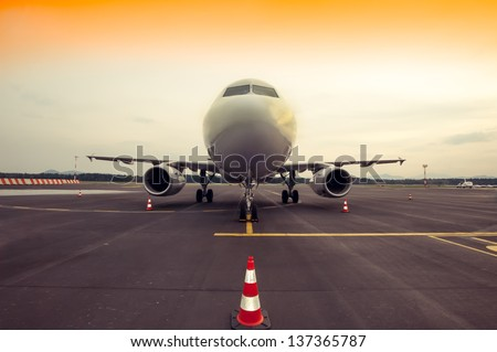 Commercial airplane parking at the airport - front, with traffic cone - stock photo