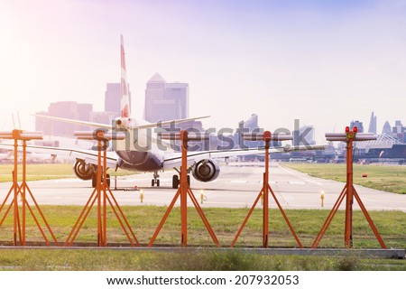 Commercial airplane preparing for take-off at London City Airport with Canary Wharf in the background - stock photo