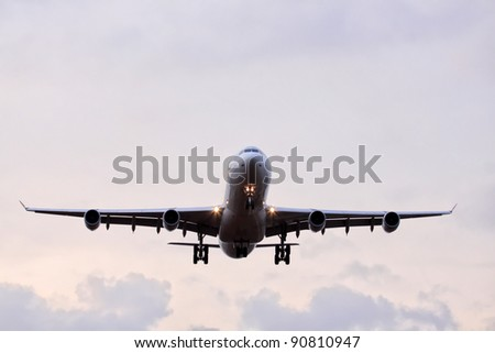 Commercial airplane with four engines in final approach front view - stock photo