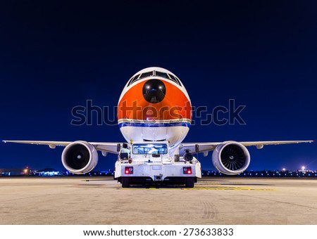 Commercial airplane with pushback car - stock photo