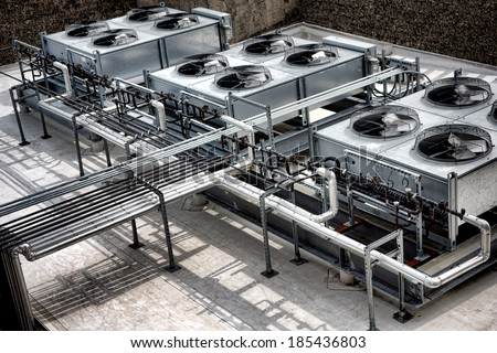 Commercial cooling HVAC air conditioner condenser fan units battery set on large commercial building rooftop for climate control and refrigeration temperature AC conditioning system - stock photo