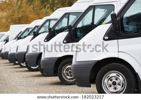 commercial delivery vans in row at parking place of transporting carrier shipping service company - stock photo