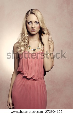 commercial fashion portrait of a young beautiful blond woman , with summer color dress and curly hairstyle, she is posing - stock photo