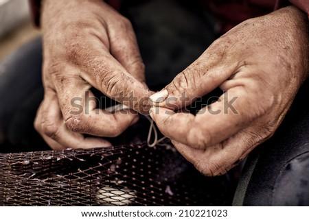 Commercial fisherman repairing his Eel nets - stock photo
