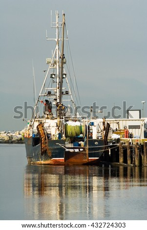 commercial fishing boat waiting at the dock - stock photo
