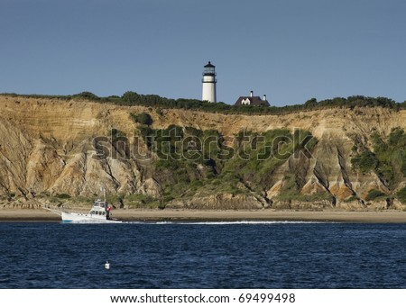 Commercial fishing vessel passing by the Truro Lighthouse in Cape Cod. - stock photo