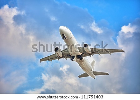 Commercial jet plane - flight in cloudy sky. White passenger airplane. - stock photo