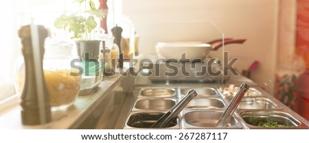 Commercial kitchen in a food bar. Variety of ingredients, sauces, spices and salads in a metal box containers. Wok pan on the wok cooker in the back. - stock photo
