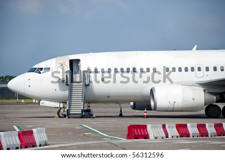 Commercial passenger aircraft, ready for boarding on the landing strip of an airport - stock photo