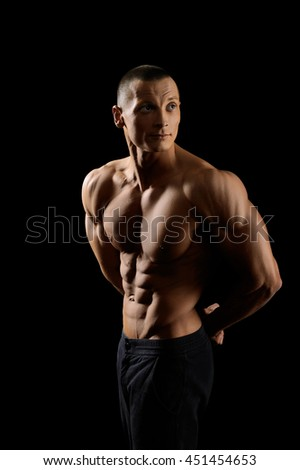 Committed to sports. Handsome young fitness man with ripped strong and toned body looking away thoughtfully  - stock photo