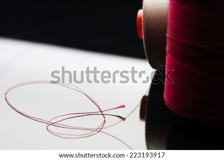 common thread, cotton yarn red leaning on white table mirror with black shade. spool of red cotton - stock photo