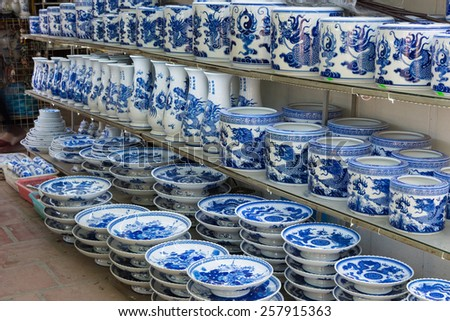 Common traditional pottery products on a shop in Bat Trang ancient ceramic village. Bat Trang village is the oldest and best known pottery village of Vietnam. - stock photo