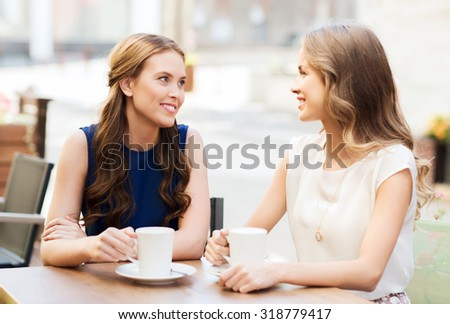 communication and friendship concept - smiling young women with coffee cups at cafe - stock photo