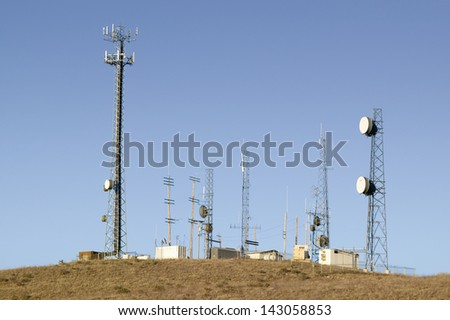 Communication antenna and cell towers clustered on hill near Cuyama, California - stock photo