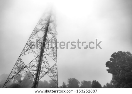 communication antenna tower in the mist - stock photo
