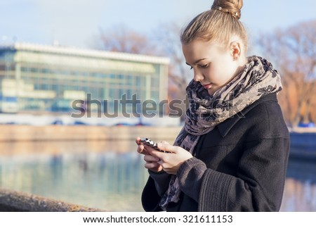 Communication Concept. Young Caucasian Teenage Girl Speaking on Cellphone.Posing Outdoors in Trendy Coat. Horizontal Image Composition - stock photo