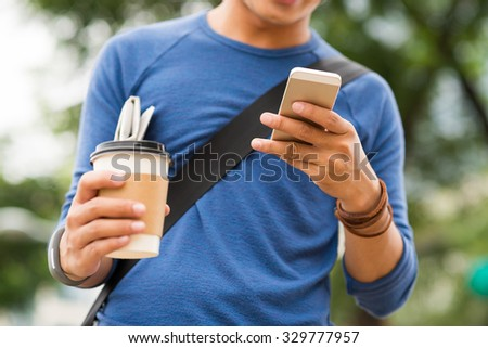 Communication concept: young man checking his phone when going to work - stock photo
