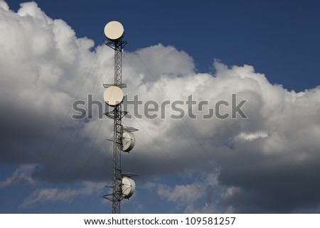 Communication tower completely surrounded by cloudy blue sky. Plenty of room for text. - stock photo