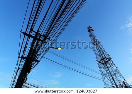 Communication tower under blue sky with clouds - stock photo