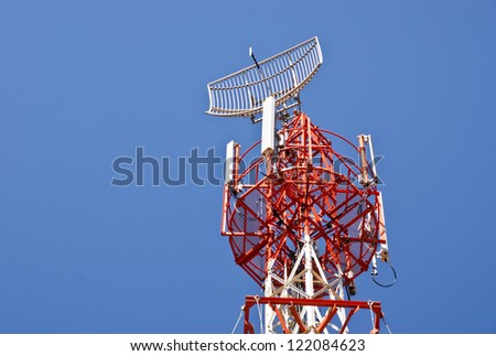 communication tower  with different antennas against  blue sky - stock photo
