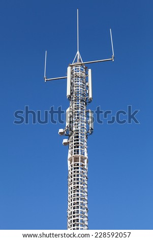 Communication tower with GSM and radio devices above blue sky - stock photo
