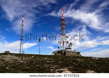 Communications center with several kind of antennas and  red and white towers - stock photo