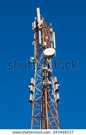 Communications tower with antennas against blue sky - stock photo
