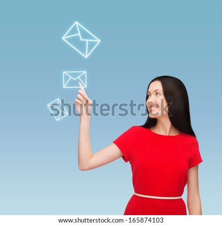 communiction and new technology concept - attractive young woman in red dress pointing her finger at envelope - stock photo