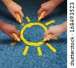 Community education and children learning and development concept with a group of hands representing ethnic groups of young people holding chalk cooperating together as friends to draw a yellow sun. - stock photo