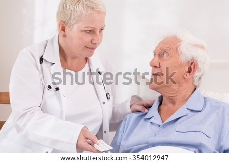 Community nurse giving pills to a senior patient - stock photo