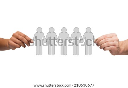 community, unity and teamwork concept - multiracial couple hands holding paper chain people - stock photo