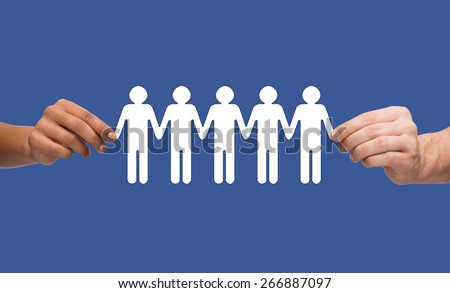 community, unity and teamwork concept - multiracial couple hands holding paper chain people over blue background - stock photo
