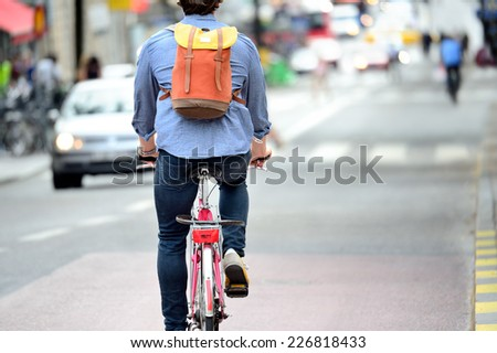 Commuter on bike in traffic - stock photo