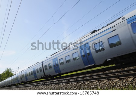 commuter train at full speed, tilted perspective. - stock photo