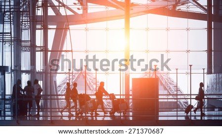 commuters walking in modern airport, back light - stock photo