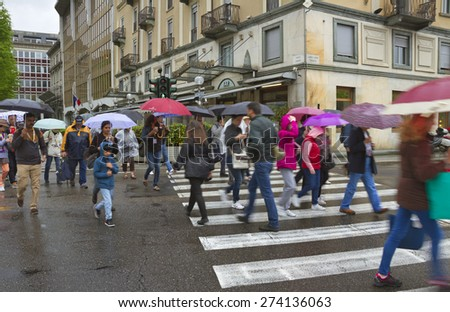 COMO, ITALY - APRIL 27: View to the Como. Its proximity to Lake Como and to the Alps has made Como a popular for tourist.  Group of people going across the street in rain on 27 April 2015, Italy. - stock photo