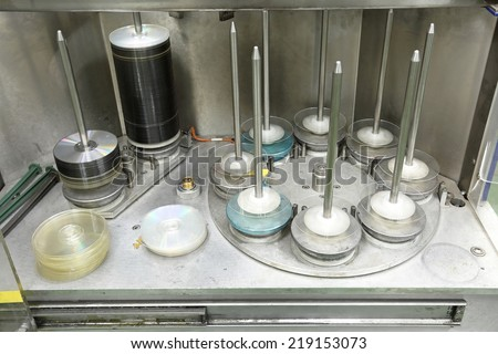 Compact disc and DVD at spindles in factory - stock photo