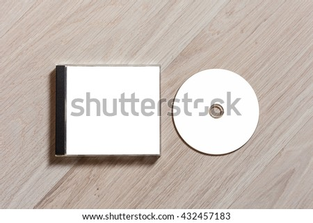 Compact disc template with plastic box with white isolated blank for branding design. CD jewel case mock up with clean free space with booklet for print on wooden table. Top view - stock photo