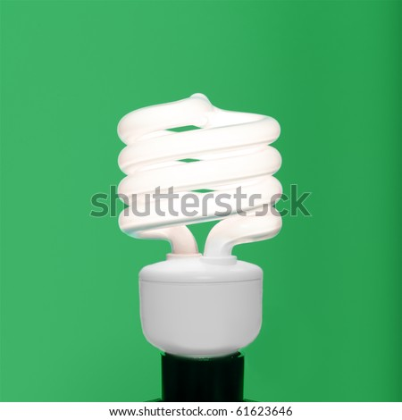Compact fluorescent bulb against a green background - stock photo