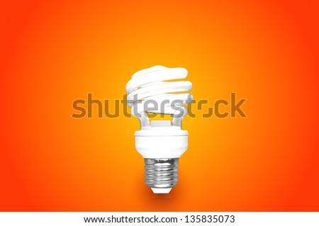 Compact Fluorescent Bulb on orange background (CFL) - stock photo