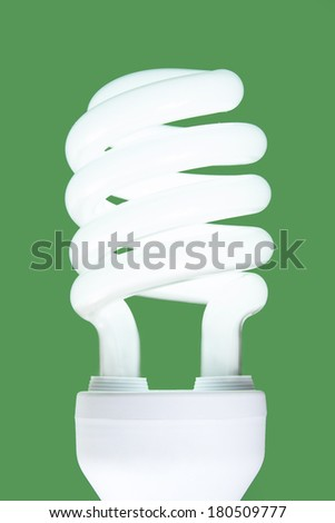 Compact fluorescent lamp. Green background, ecological metaphor. - stock photo