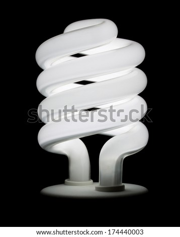 Compact fluorescent light bulb lit against a black background isolated - stock photo