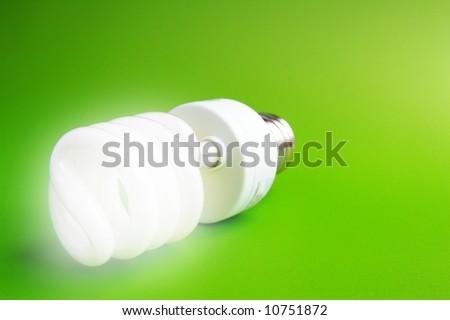 Compact fluorescent light bulb on green (green energy) - stock photo