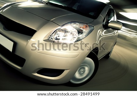 Compact hatchback closeup driving fast in parking house - stock photo