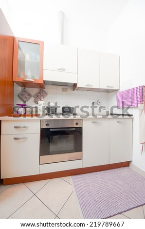 Compact kitchen interior with wooden cabinets and a built in stove and gas hob with kitchen utensils on the counter and a tiled floor - stock photo