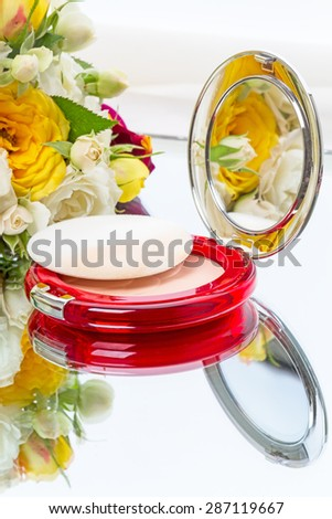Compact powder mirror and flower bouquet on white background - stock photo