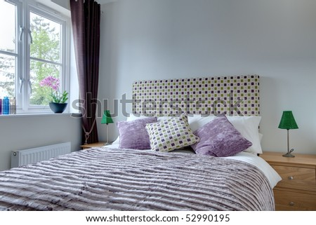 Compact stylish modern bedroom with brightly colored quilt, headboard and matching cushions - stock photo